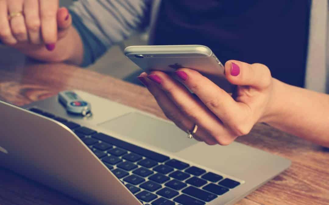 femme sur son smartphone devant un ordinateur