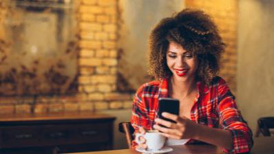 Femme souriant qui tient un téléphone dans la main